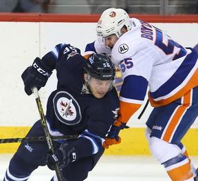 Winnipeg Jets center Marko Dano (left) is tied up by New York Islanders defenceman Johnny Boychuk. Dano has been resigned by the Jets. (Brian Donogh/Winnipeg Sun files)