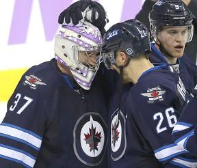 Winnipeg Jets goalie Connor Hellebuyck is congratulated by right winger Blake Wheeler after shutting out the Chicago Blackhawks during NHL hockey in Winnipeg on Nov. 15, 2016. (Brian Donogh/Winnipeg Sun/Postmedia Network)