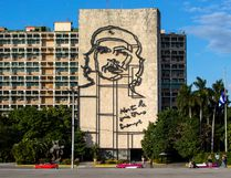 "Tourists walk by the iconic image of Cuba's revolutionary hero Ernesto ""Che"" Guevara, at Revolution Square near the Ministry of Interior in Havana, Cuba, Sunday, Nov. 27, 2016. (AP Photo/Desmond Boylan)"
