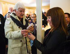 Dar Antonation (left) hands Stacey Fitzgerald the key to her new house Nov. 19. (Brook Jones, Interlake Publishing, Postmedia Network)