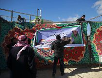 Palestinians hang a banner