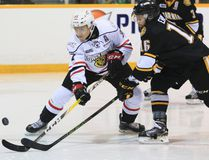 Owen Sound Attack's Nick Suzuki tries to get a shot off under pressure by the Sarnia Sting's Jordan Ernst during Ontario Hockey League action earlier this season.
