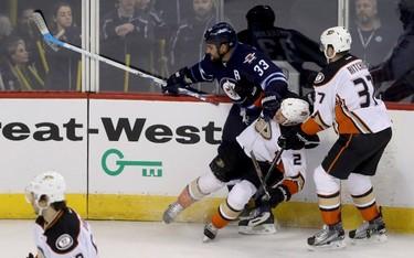 Winnipeg Jets' Dustin Byfuglien (33) shoves Anaheim Ducks' Kevin Bieksa (2) to the ice during third period NHL hockey action in Winnipeg, Monday, January 23, 2017. THE CANADIAN PRESS/Trevor Hagan