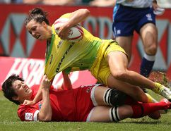 Napanee's Britt Benn, bottom, brings down Australia's Emilee Cherry during a women's semifinal match at the World Rugby Sevens Series tournament in Sydney, Australia, on Saturday. (Rick Rycroft/The Associated Press)
