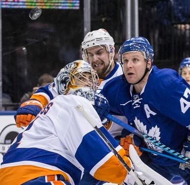 Toronto Maple Leafs center Leo Komarov (47) looks up at the puck over New York Islanders goalie Thomas Greiss (1)  in Toronto on Tuesday February 14, 2017. Craig Robertson/Toronto Sun/Postmedia Network