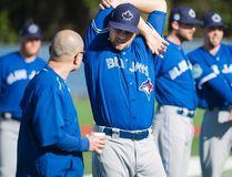 Toronto Blue Jays pitcher Glenn Sparkman, centre, talks with a trainer during spring training in Dunedin on Feb. 16, 2017. (THE CANADIAN PRESS/Nathan Denette)