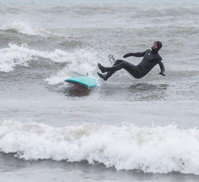 Hugh Whitaker takes a spill off his surf board in Lake Ontario at Ashbridges Bay. Whitaker was enjoying the blast of winter in Lake Ontario  on Tuesday March 14, 2017. Craig Robertson/Toronto Sun/Postmedia Network