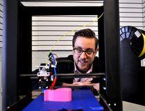 Titus Ferguson, executive director of UnLondon, peers through a 3D printer at 121 Studios in London Ont. March 16, 2017. CHRIS MONTANINI\LONDONER\POSTMEDIA NETWORK