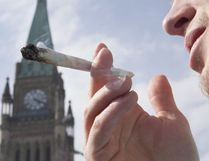 A demonstrator smokes a marijuana joint on Parliament Hill in Ottawa on April 20, 2010. THE CANADIAN PRESS/Pawel Dwulit