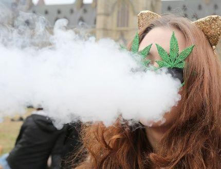 A woman smokes marijuana on Parliament Hill on 4/20 in Ottawa, April 20, 2017. (LARS HAGBERG/AFP/Getty Images)