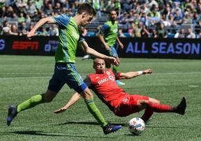 Toronto FC defender Jason Hernandez tries to block a shot by Seattle Sounders midfielder Alvaro Fernandez on Saturday. (AP)