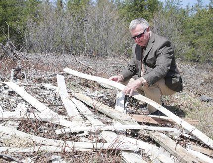 Ward 5 Coun. Robert Kirwan on Wednesday surveys garbage dumped in the woods near Frappier Street in Val Caron, Ont. on Wednesday. Gino Donato/Sudbury Star/Postmedia Network