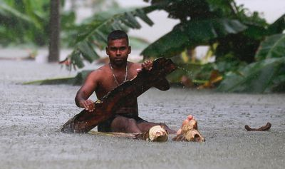 A Sri Lankan man rows a makeshift raft on a flooded road in Wehangalla village in Kalutara district, Sri Lanka, Saturday, May 27, 2017.  (AP Photo/Eranga Jayawardena)