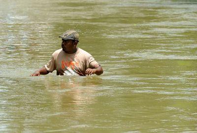 A Sri Lankan man walks through floodwaters in Bulathsinhala in Kalutara districton May 27, 2017. (LAKRUWAN WANNIARACHCHI/AFP/Getty Images)