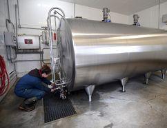 A dairy farmer checks a milk tank on a farm in Eastern Ontario in this file photo. Postmedia Network