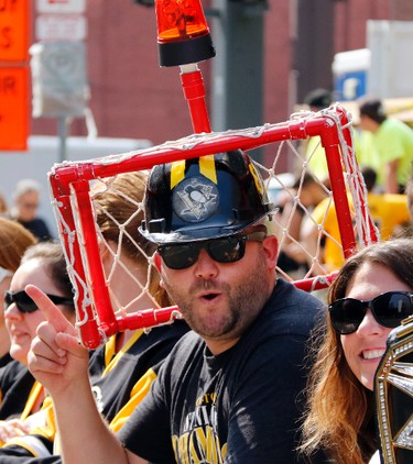 Pittsburgh Penguins fan Matt Nesbella, center, of Pittsburgh, waits for the start of the Penguins' NHL hockey Stanley Cup victory parade in Pittsburgh, Wednesday, June 14, 2017. (AP Photo/Gene J. Puskar)