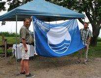Bluewater Deputy Mayor Jim Fergusson and Mayor Tyler Hessel proudly pose with Bayfield's Blue Flag.