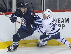 Winnipeg Jets right winger Patrik Laine takes down Toronto Maple Leafs centre Auston Matthews during NHL action in Winnipeg on Oct. 19, 2016. (Brian Donogh/Winnipeg Sun/Postmedia Network)