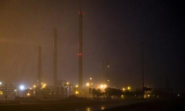 An oil refinery's lights illuminate rainfall as Hurricane Harvey makes landfall in Corpus Christi, Texas, on Friday, Aug. 25, 2017. (Nick Wagner/Austin American-Statesman via AP)