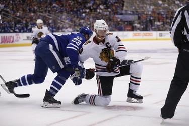 Jonathan Toews battles Eric Fehr of Toronto as Leafs host Chicago at the ACC in Toronto on Monday October 9, 2017. Michael Peake/Toronto Sun/Postmedia Network