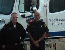 Blue Ridge Fire Chief Gerry Bizier (left) and deputy chief Kaj Christensen stand next to a new fire truck their department recently received (Joseph Quigley | Mayerthorpe Freelancer).