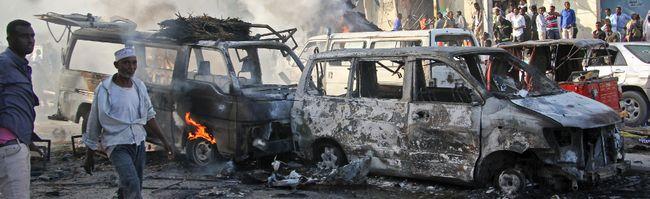 Somalis walk past the wreckage of vehicles