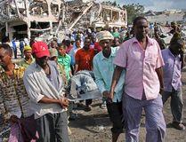 Somalis remove the body of a man killed in Saturday's blast, in Mogadishu, Somalia Sunday, Oct. 15, 2017. (AP Photo/Farah Abdi Warsameh)