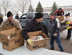 Volunteers help load Christmas Baskets last year. (Expositor photo)