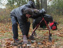 Travis Canadien picks up garbage on Belle Island on Saturday. (Steph Crosier/The Whig-Standard)