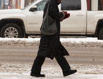 IAN KUCERAK Postmedia Network - A pedestrian walks along Whyte Avenue near Calgary Trail last November. The City of Edmonton is starting its public consultation on Strathcona neighbourhood renewal.