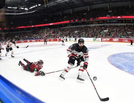 Latvia's Kirils Tambijevs, left, and Canada's Eric O'Dell fight for the puck during an exhibition hockey game in Riga, Latvia, Sunday, Feb. 4, 2018. (AP Photo/Roman Koksarov)