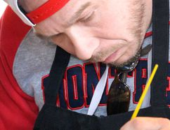 Shane Neggers focuses as he tries stenciling at Creative Nest Studio's exhibit.