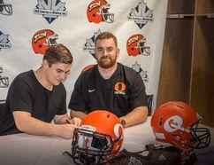 <p>Jakob Loucks, signing with the Okanagan Sun, with head coach Ben Macauley (right).</p><p> Handout/Cornwall Standard-Freeholder/Postmedia Network