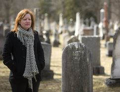 History professor Michelle Hamilton stands among First World War-era gravestones at London's Woodland Cemetery. (MIKE HENSEN, The London Free Press)