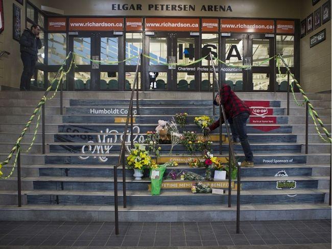 A man drops of flowers at a memorial located inside the Elgar Petersen Arena in Humboldt, SK on Saturday, April 7, 2018. (Saskatoon StarPhoenix/Kayle Neis)