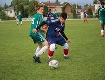 Tate Trueman attempts to fight off an FC Sting defender.