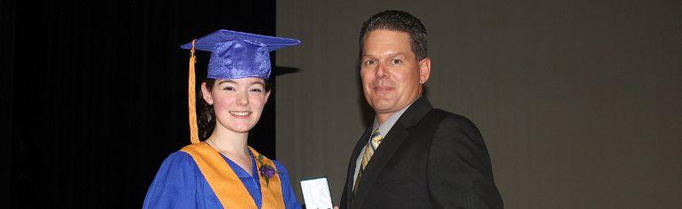 ECJV graduating student and class valedictorian Emilie Godin receives her diploma from Principal Steve Guertin.