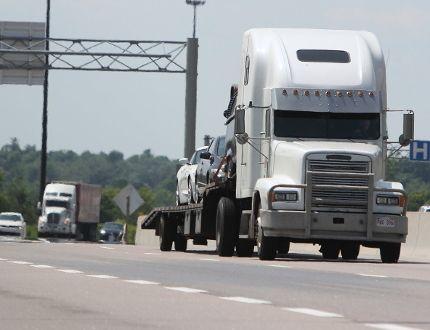 Transport trucks travel Highway 401 in Kingston on Thursday. (STEPH CROSIER/Postmedia network)