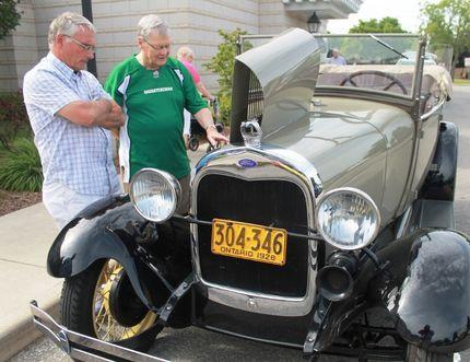 Bluewater Austin-Healey Club member Bruce Scott shows off his 1928 Model A Ford Phaeton to Landmark resident Marvin Bildfell. CARL HNATYSHYN/SARNIA THIS WEEK