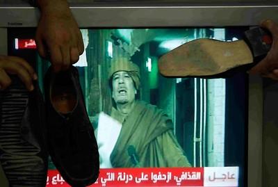 Jordanians hit with their shoes a TV showing Libya's leader Muammar Gaddafi giving a speech, in Amman February 22, 2011. REUTERS/Ali Jarekji