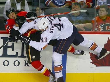 Edmonton Oilers Jason Strudwick hits Calgary Flames Stefan Meyer during first period action between the Edmonton Oilers and the Calgary Flames in Calgary October 3, 2010. (Jim Wells/ QMI Agency)