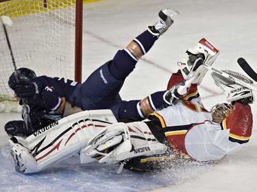 The Calgary Flames Henrik Karlsson gets run in to by Edmonton Oilers Liam Reddox during NHL action at Rexall place. (JORDAN VERLAGE/EDMONTON SUN)
