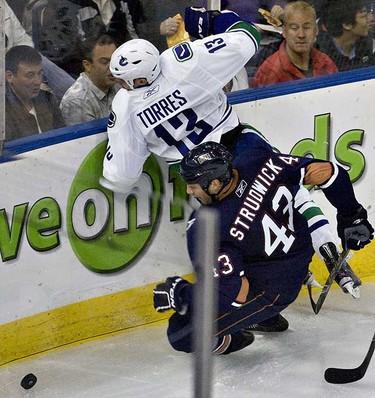 Edmonton Oilers Jason Strudwick collides with Vancouver Canucks Raffi Torres during second period NHL preseason action at Rexall Place on Sunday, September 26 2010, in Edmonton, Alta. (AMBER BRACKEN/EDMONTON SUN)