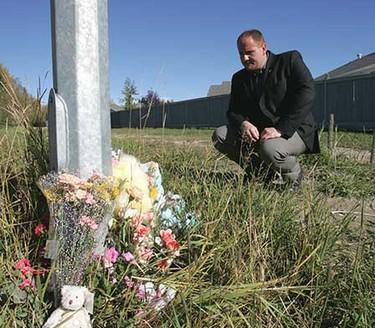 Sept. 29, 2008: Edson Mayor Greg Pasychny looks over a memorial set up near the crime scene in Edson. (Robert Taylor/Sun Media)