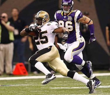 New Orleans Saints running back Reggie Bush is pursued by Minnesota Vikings defensive end Brian Robison.  (REUTERS/Sean Gardner)