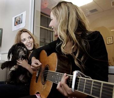Canadian country music duo Sharlene (l) holds Annabelle as Jolene (r) Keats plays the guitar on a visit to the Edmonton Humane Society.  (DOREEN THUNDER/EDMONTON SUN)