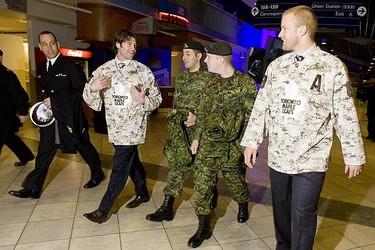 Toronto Maple Leafs defencemen Jeff Finger and Mike Komisarek take Evan Lapointe and Tolga Oken - both of 7th Toronto Regiment - for a tour of their dressing room. (GREG HENKENHAF, Toronto Sun)