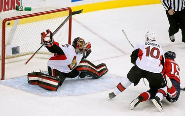 Washington Capitals' Boyd Gordon (R) scores a goal on Ottawa Senators' goalie Pascal Leclaire (L) as he is checked by Senators' Shean Donovan during first period NHL hockey action in Washington on Jan. 7, 2010. (REUTERS)