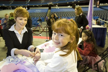 Kim Duquette makes up 6 year old Hannah Basile. (Toronto Sun/Stan Behal)
