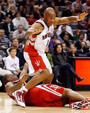 Toronto Raptors guard Jarrett Jack (top) falls over Houston Rockets forward Carl Landry during the second half of their NBA basketball game in Toronto on Dec. 13, 2009. (REUTERS)